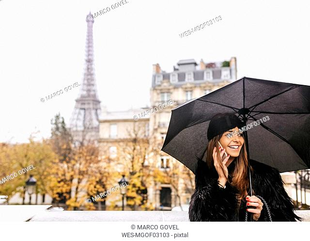 France, Paris, young woman talking on cell phone under umbrella with the Eiffel Tower in the background