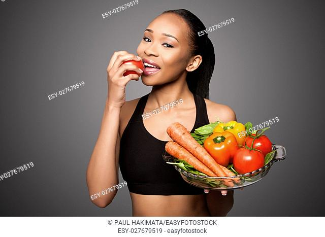 Beautiful healthy happy black asian woman eating delicious vegetables