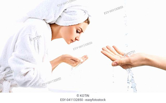 Woman with towel on head washes up her face near stream water. Isolated on white