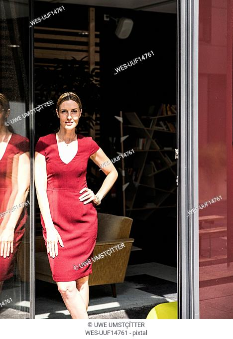 Woman wearing burgundy dress standing at the window in sunshine