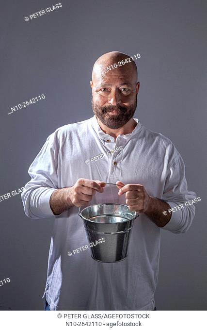 Middle age bald man with a beard, holding a metal bucket