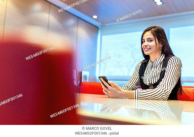 Portrait of smiling businesswoman sitting in a conference room with her smartphone