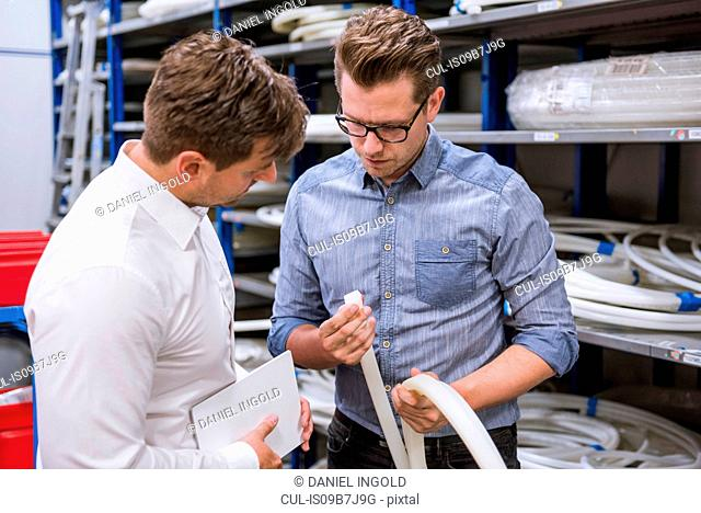 Male managers inspecting product in factory warehouse
