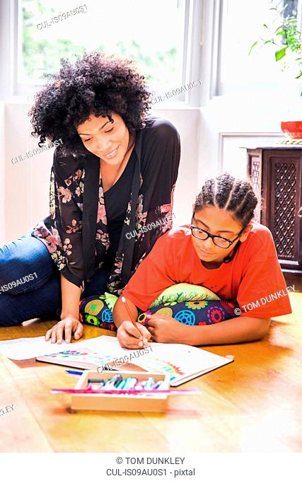 Mature woman and son drawing in sketchbook on living room floor