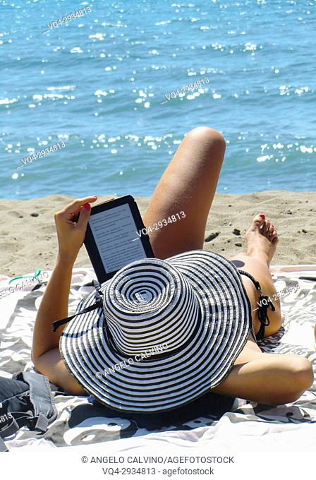 Girl with large circular hat reading on kindle system in front of the sea