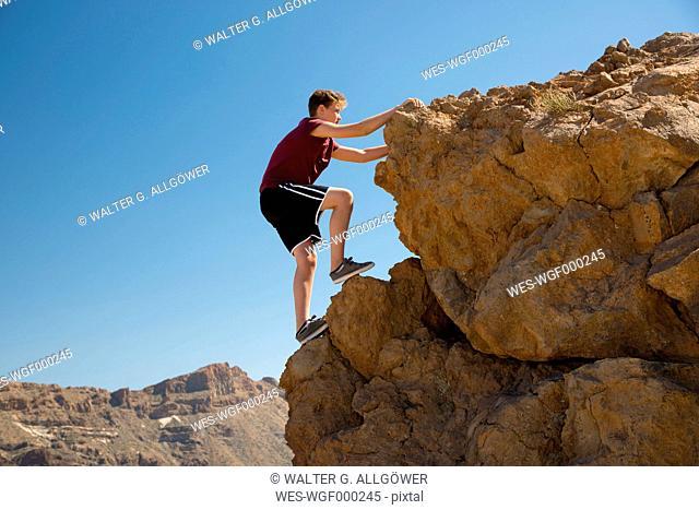 Spain, Canary Islands, Tenerife, Teide National Park, boy climbing on rock