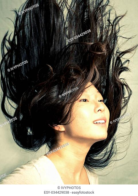 Young woman flicking her hair and posing, with fashion tone and background
