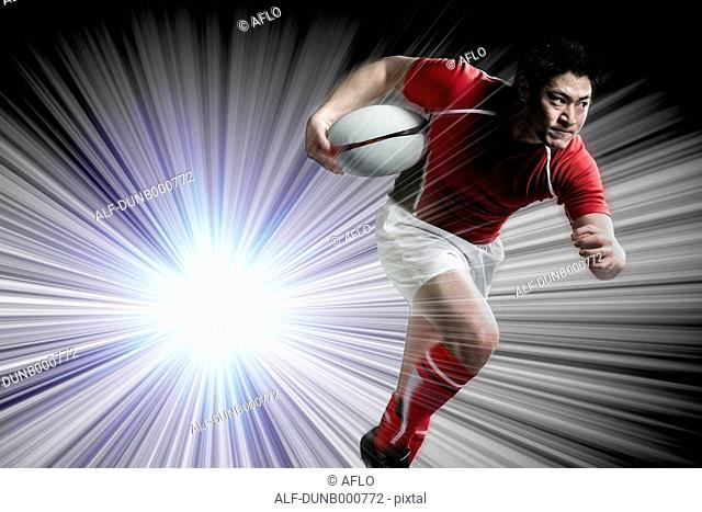 Portrait of Japanese rugby player running with ball