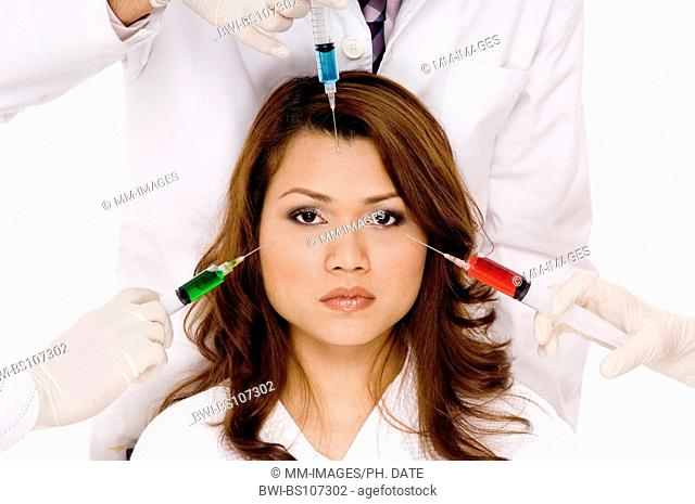 young pretty Asian woman with three needles about to be put into her face