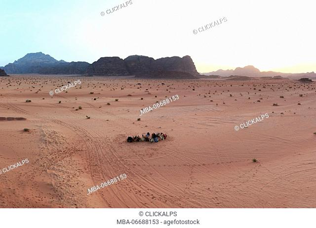 Sunset in the Wadi Rum desert, Jordan, with local bedouins and camels on foreground