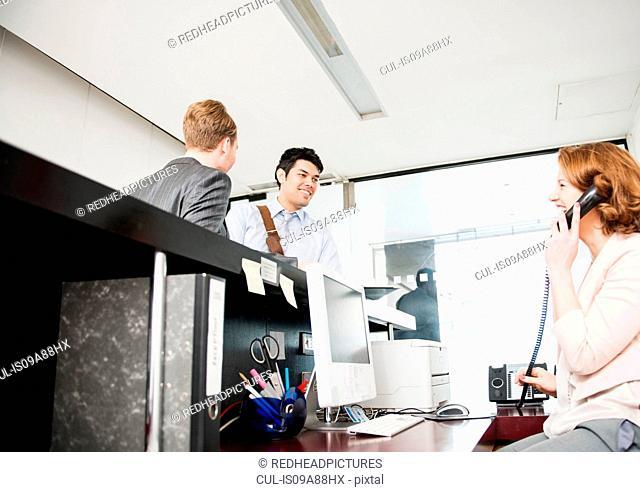 Two men at reception and woman on telephone
