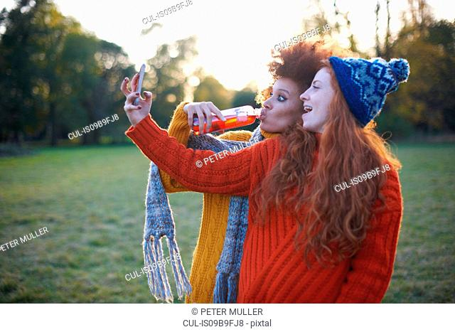 Two young women, in rural setting, taking selfie, using smartphone