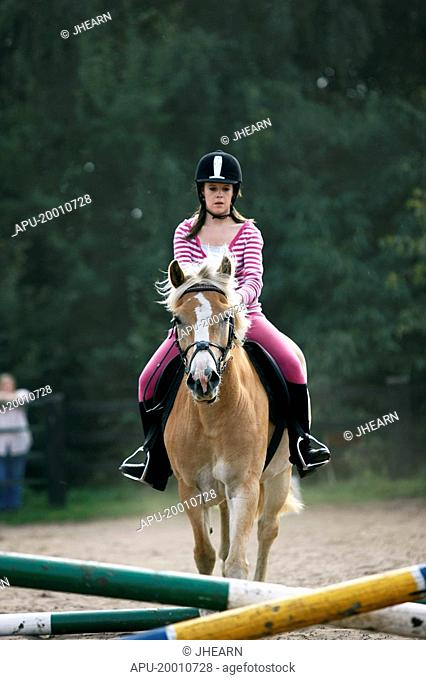 Girl in hard hat training her pony in jumping