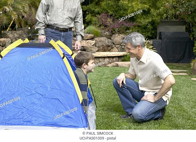 Father and son with tent in backyard