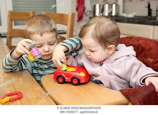 Two children, 3 and 1 years, playing together with a toy car