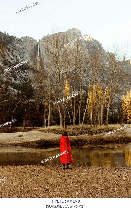 Rear view of woman wrapped in red blanket looking out at mountain, Yosemite National Park, California, USA