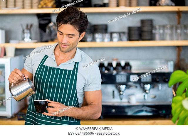Smiling waiter pouring a cup of coffee