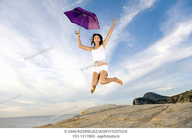 Happy brunette woman with umbrella jumping in a cliff by the sea in Ibiza