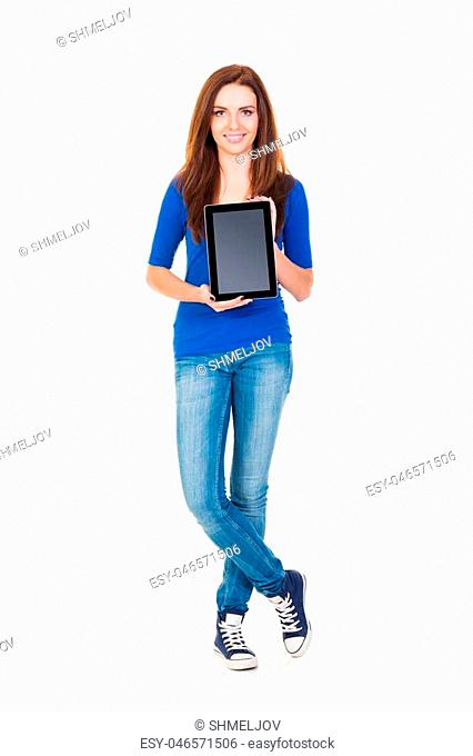 A young and happy girl in stylish jeans holding a tablet computer isolated on a white background