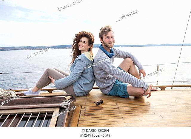 Young couple on yacht sitting back to back