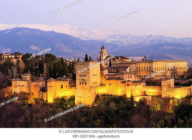 Illuminated Alhambra palace and Sierra Nevada at sunset. Granada, Andalusia, Spain