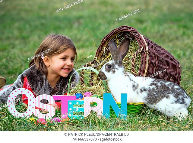 ILLUSTRATION: The five-year-old girl Mia on a meadow with a rabbit and an Easter basket full of colored eggs in Sieversdorf (Brandenburg), Germany