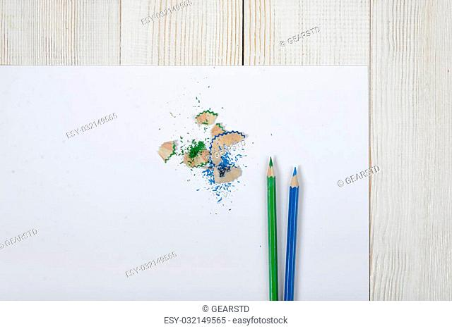Flat lay of different colored pencils and shavings with white paper. Work place