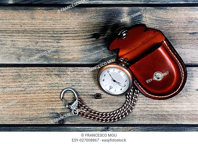Picture of a antique pocket watch with case of old wood background
