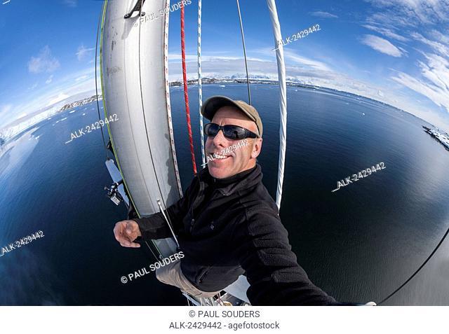 Antarctica, Self-portrait of Photographer Paul Souders climbing mast of sailboat Sarah Vorwerk while sailing near Palmer Antarctic Station on sunny day
