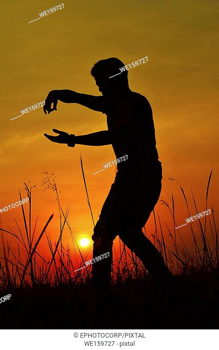 Silhouette of a Hip Hop Dancer posing near mountain at sunset, Pune, Maharashtra