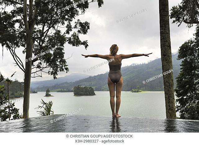 young woman standing on the edge of the swimming pool of the Summerville Bungalow overlooking the Castlereagh Lake, luxury Ceylon Tea Trails resort, near Hatton