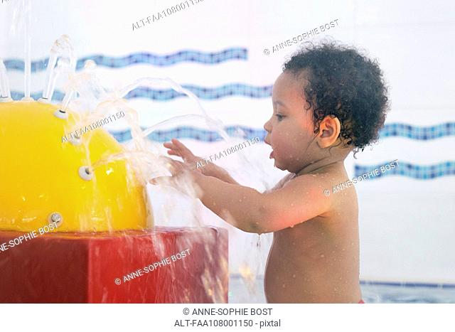 Little girl playing in fountain in wading pool