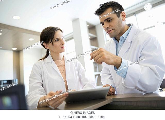 Dentists talking with digital tablet at front desk