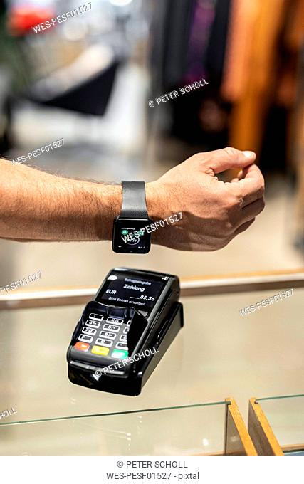Customer paying contactless with his smartwatch