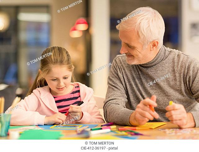 Father and daughter bonding, doing crafts at table