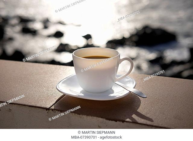 Coffee cup on wall in front of sea, Valle Gran Rey, La Gomera, Canary Islands, Canary Islands, Spain