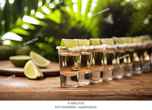 Gold tequila shots with lime fruits on wooden and green tropical leaves background