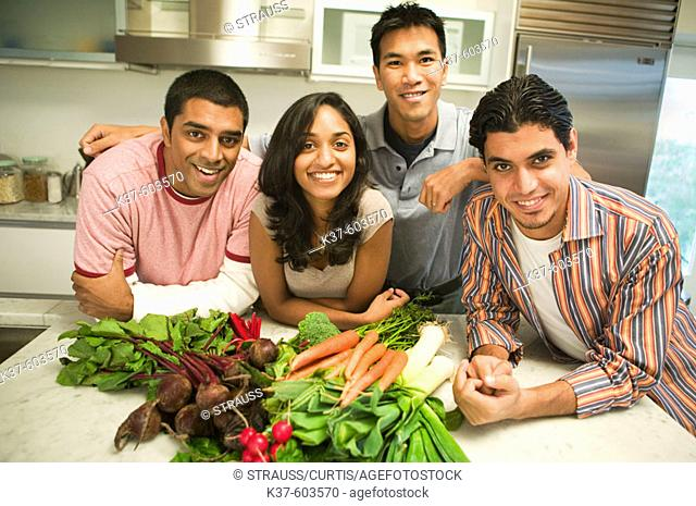 Group of young people of mixed ethnicities holding vegetables in kitchen