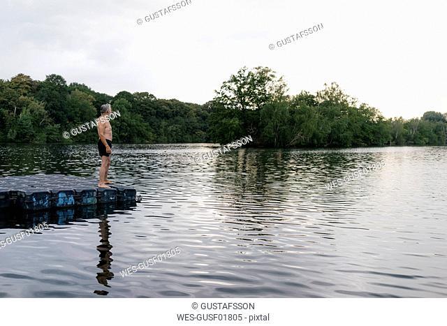 Senior man standing on raft in a lake
