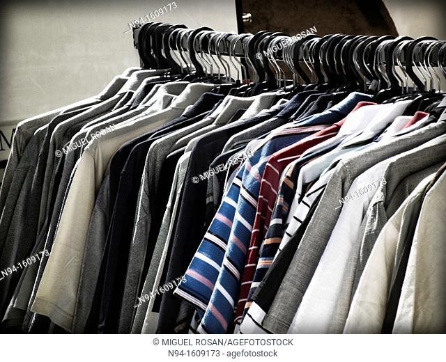 Hangers with shirts and men's clothing in summer
