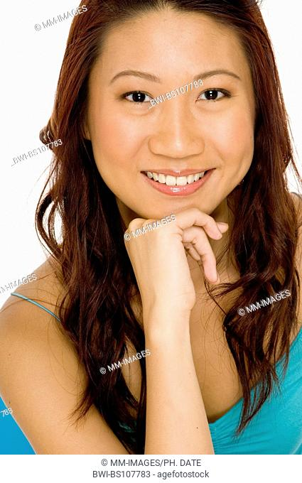 A beautiful young asian woman with chin resting on hand