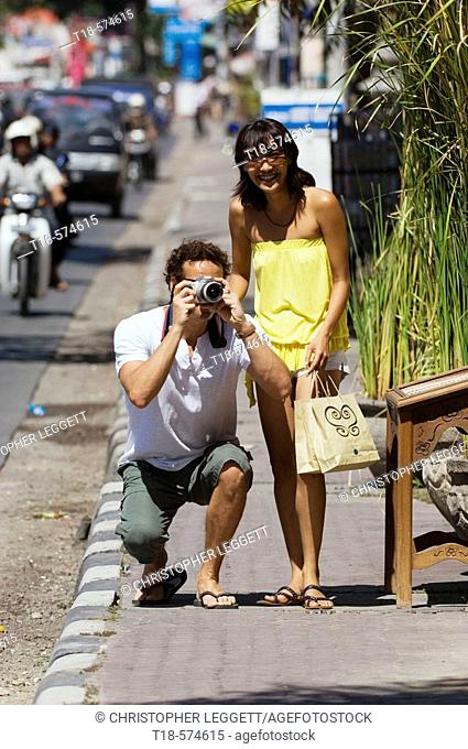 couple taking snapshot on sidewalk