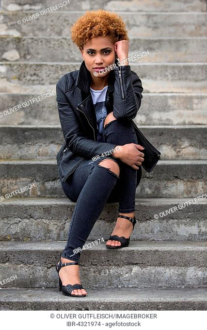 Young dark woman sitting on a stone staircase, fashion, portrait