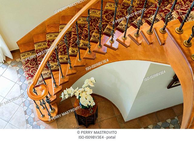 Top view of wooden spiral staircase, burgundy and cream coloured rug runner and brass rods