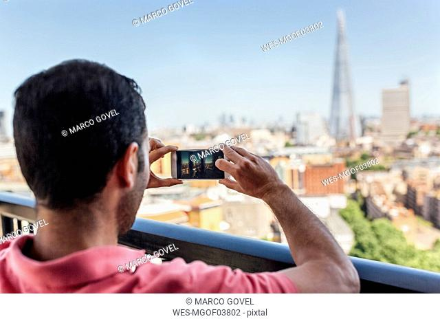 UK, London, man taking a picture of the city from roof terrace