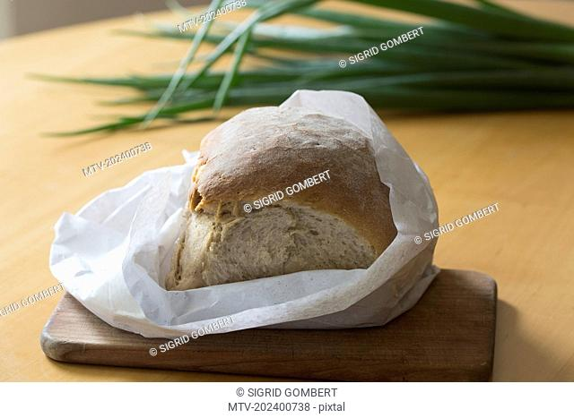 Bread loaf wrapped in paper on the table, Freiburg im breisgau, Baden-württemberg, Germany