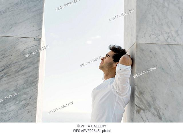 Man wearing white shirt leaning against marble column looking up