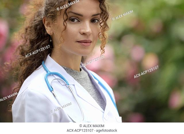 Portrait of a young woman, doctor, physician, medical practitioner in lab coat in natural outdoor settings