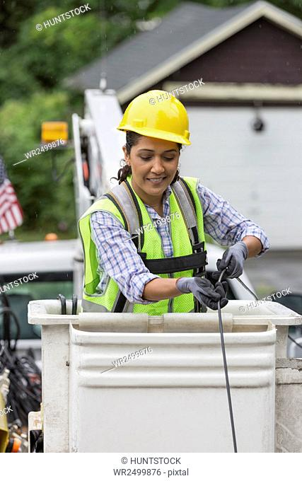 Hispanic female cable lineman stringing a new line