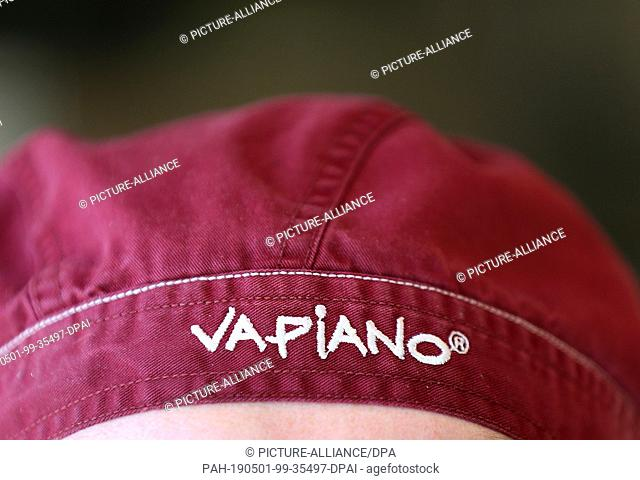 30 April 2019, North Rhine-Westphalia, Cologne: An employee with a cap bearing the words Vapiano is standing behind the counter in a branch of the restaurant...
